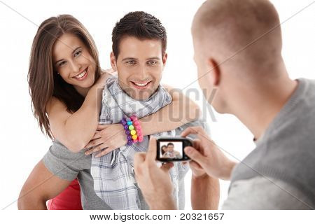 Friend taking photo of happy couple smiling and hugging, isolated on white.?