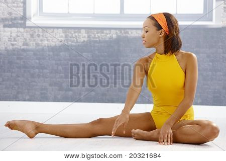 Ballet dancer concentrating on stretching on floor of art training room.?