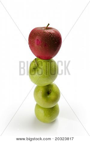 Green apples balanced on top of one another with a red apple on top with moisture