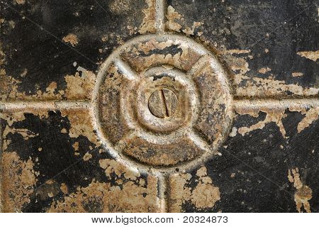Bottom of an old worn black metal container with a screw head in the center