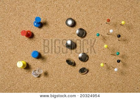 Pins and tacks on a cork board