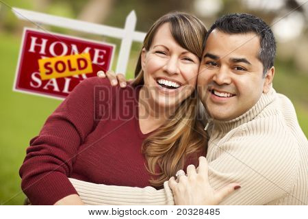 Happy Mixed Race Couple in Front of Sold Real Estate Sign.