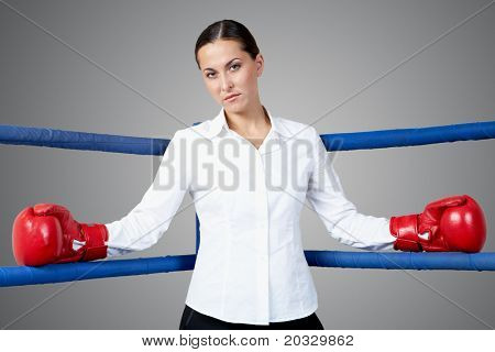 Portrait of strict businesswoman in boxing gloves looking at camera