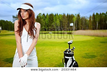 Young brunette woman with golf equpment