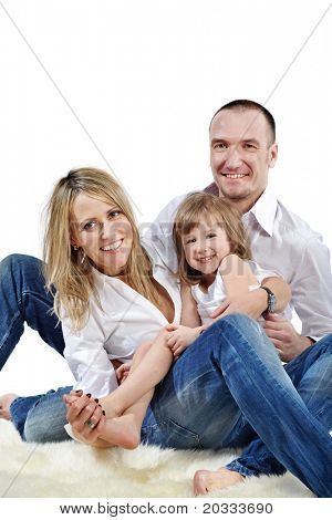 Father embraces daughter and wife sitting on the white shaggy carpet.