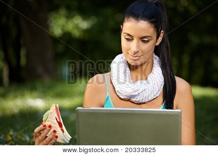 Young woman in park at lunchtime, using laptop, eating club sandwich.?