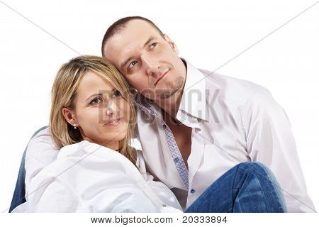 Closeup young woman and man in white shirts and blue jeans sit on the floor and slightly smiling look in one direction.