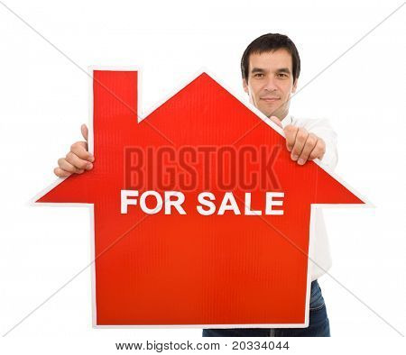 Confident salesman holding house for sale sign - isolated