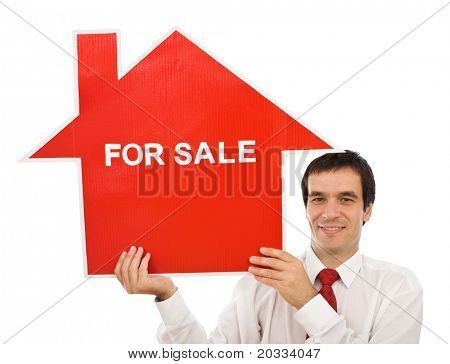 Salesman smiling holding house for sale sign - isolated