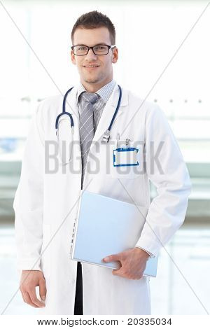 Portrait of smiling young doctor standing on hospital corridor holding laptop, looking at camera.?