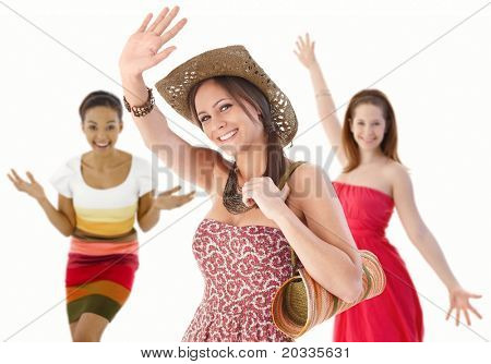 Group of happy young women waving hands in summer dresses.?