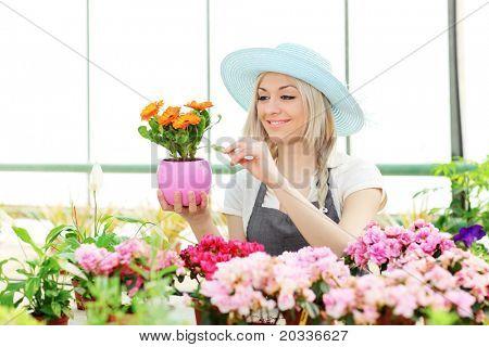 Female gardener examining flower in a garden