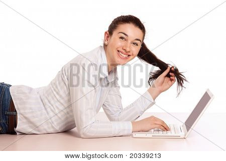 A young girl with a laptop lying on the floor, side-view