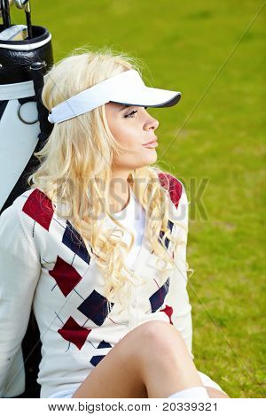 A beautiful blond haired blue eyed young woman playing golf