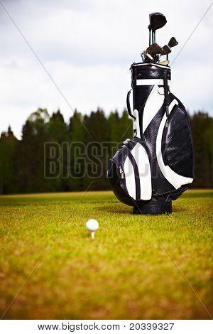 equipamento de golfe em verde e buraco como plano de fundo