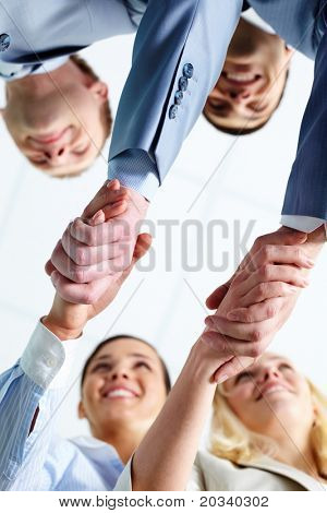 Two pairs of successful associates handshaking after striking deal with partners
