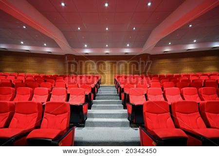 Rows of red arm-chairs are in  empty hall