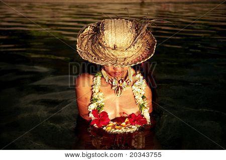 A beautiful asian woman sitting in the polynesian waters in Tahiti.