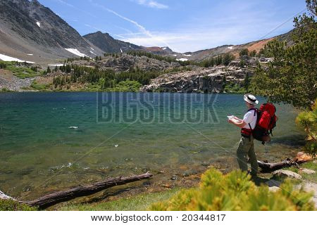 Young hiker checking his map in front of Yosemite lake