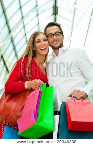 Couple - man and woman - in a shopping mall with colorful bags