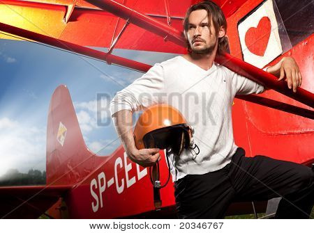 Handsome man posing next to aero-plane