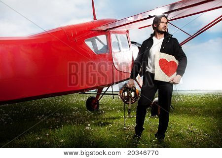 Man holding a heart symbol next to aero-plane