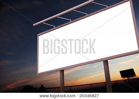 Blank illuminated billboard over evening sky