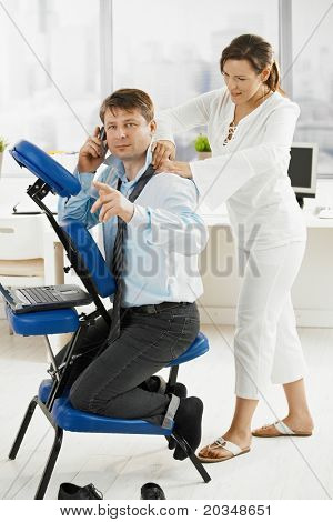 Occupied businessman talking on mobile, while masseur doing relaxing neck massage.?