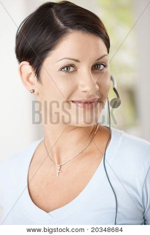 Closeup portrait of young woman wearing headset, smiling.?