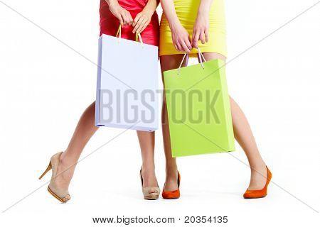 Close-up das belas pernas de compradores com paperbags sobre fundo branco