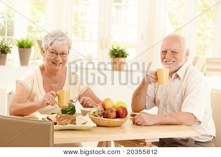 Senior couple having tea at breakfast, sitting in sunny kitchen, smiling.?