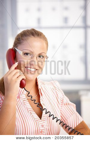 Pretty receptionist working in office, talking on phone, smiling.?