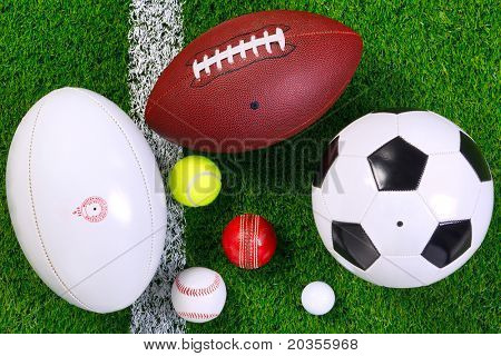 Photo of various sports balls on a grass next to the white line, shot from above.