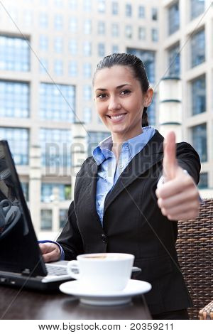 Business Woman With Thumbs Up In Restaurant