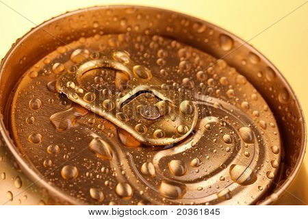 Golden metallic beer with water drops on yellow background