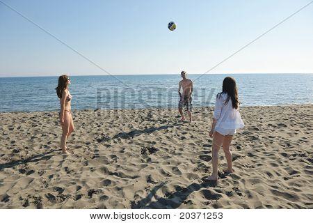 Grupo de jóvenes divertirse y jugar al voleibol de playa en un día soleado de verano