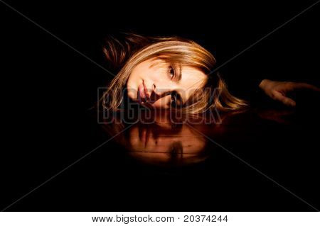 portrait of a girl reflected on the table surface