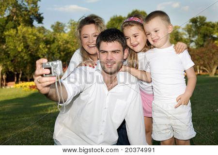 father taking a photo of whole family at the park on a sunny day