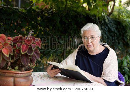 Senior Lady in 70er Jahren Lesen eines Buches im Hof ihres Hauses