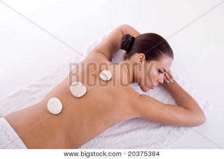 girl getting back massage with stones
