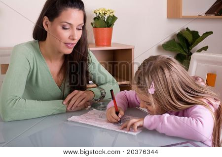 mother is helping her daughter with homework