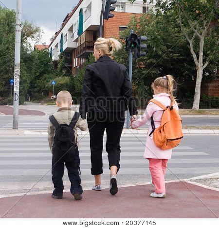 Mutter, wobei die Kinder auf der anderen Straßenseite