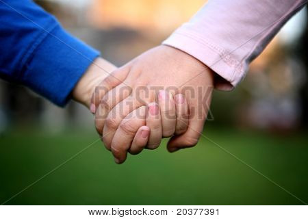 close up of two children holding hands