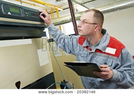 Ingeniero de mantenimiento, comprobación de datos técnicos del equipo de sistema en una casa de la caldera de calefacción