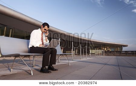 Serious business man sitting on bench, talking on mobile phone and typing on laptop computer with office building in background.