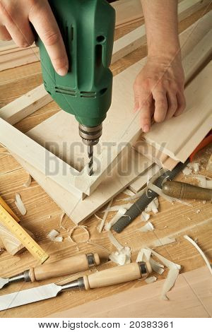 Wooden workshop table with tools. Man's arms drill plank.