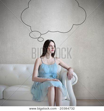 Beautiful woman sitting on a leather sofa and thinking
