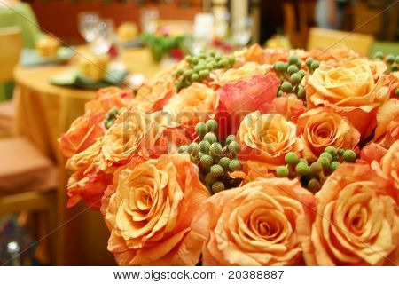 bunch of fresh orange roses in a festively decorated hall