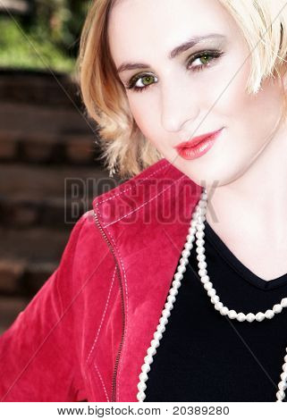 Blond business-woman with short hair in red leather jacket and pearls