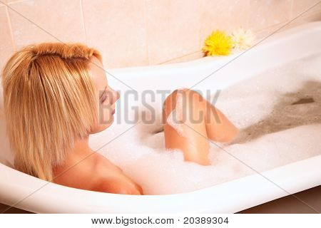 Young woman sitting in a bubble bath with her knee exposed